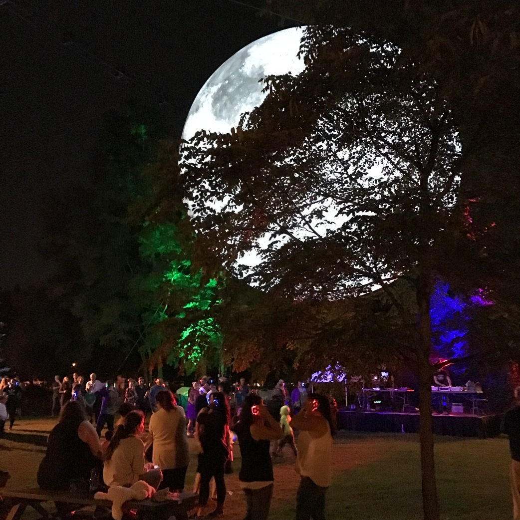 Dancers adjust their headsets for Silent Disco with the Museum of the Moon shining behind a tree.