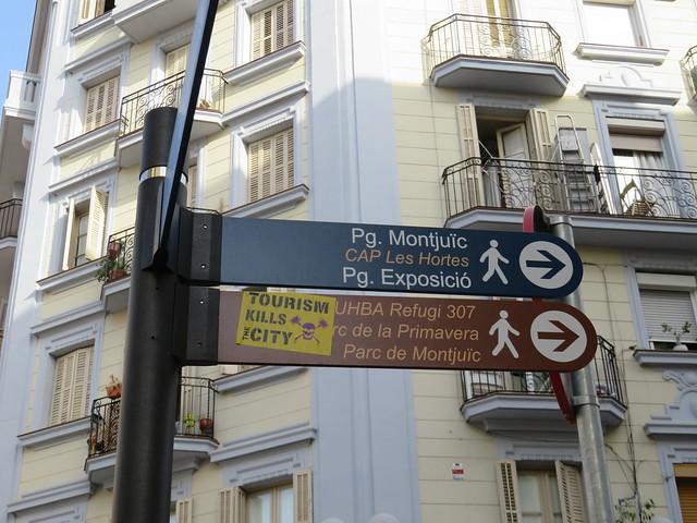 """Tourism Kills the City"" sticker on a Barcelona street sign."