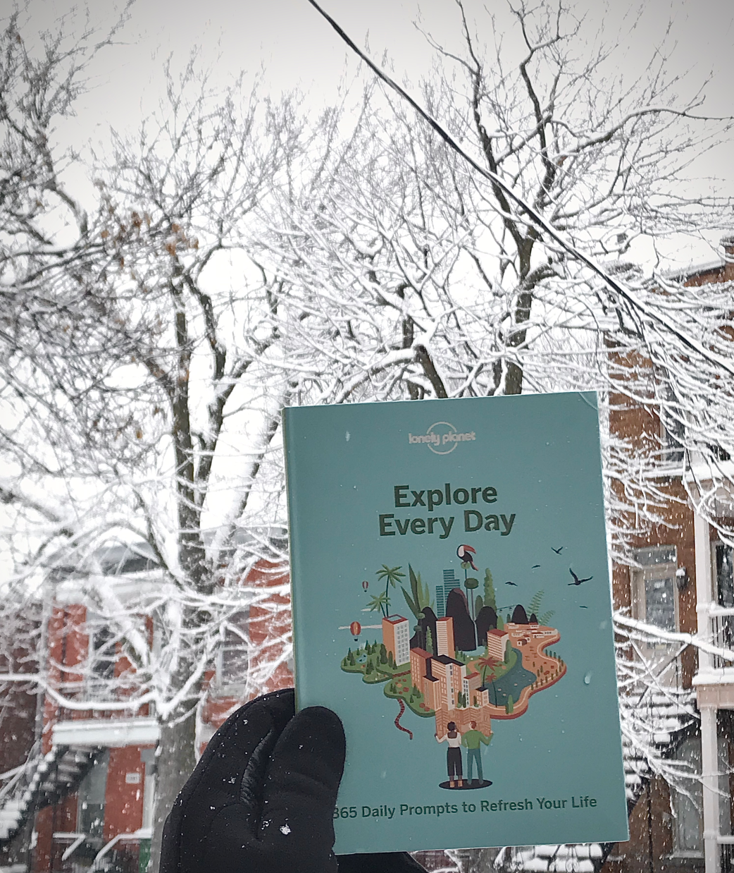 "a gloved hand holds a book titled ""Explore Every Day"""
